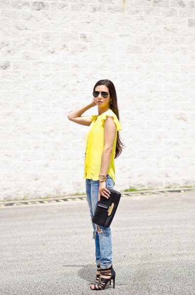 Sleeveless blouse with yellow ruffle shoulders and boyfriend jeans with cuffs