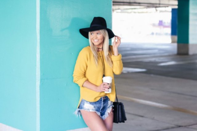 yellow sweater with blue mini-shorts made of ripped denim and floppy hat