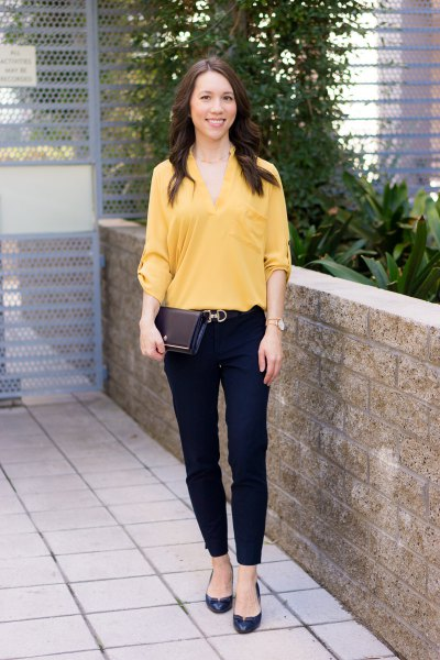 yellow blouse with V-neckline with black chinos and flats