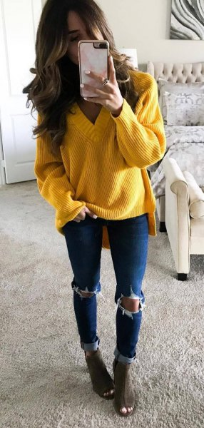 Yellow coarse knit sweater with V-neck and blue skinny jeans