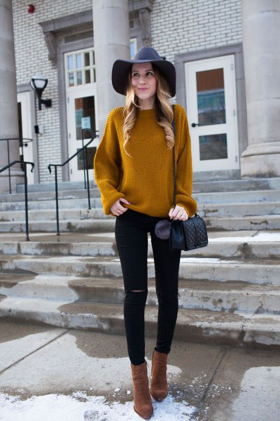 yellowish-brown ribbed sweater with black floppy hat